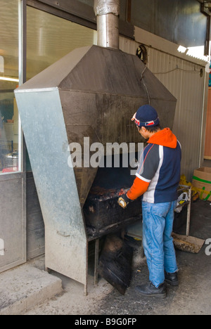 Man grilling meat at SAPA the Asia Trade Centre in Libus district in outskirts of Prague Czech Republic Europe - Stock Photo