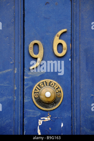 The house number 96 and a visitors' door bell button stand on the painted blue door of a London property, house, - Stock Photo