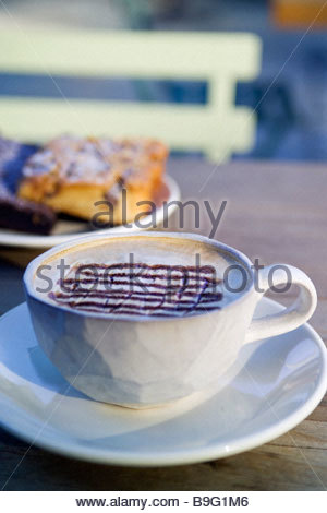 Cappuccino coffee with cakes on wooden table outdoors Terrain at Styer s 914 Baltimore Pike Glen Mills PA 19342 - Stock Photo