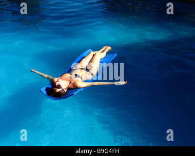 A young woman lying on a mat in a swimming pool. - Stock Photo