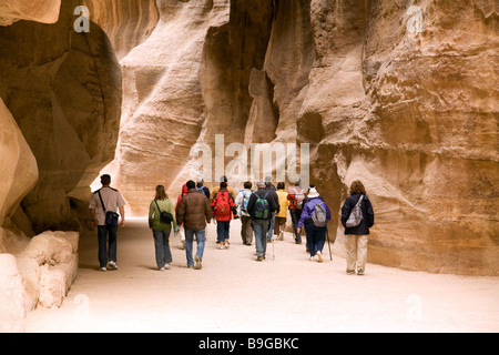 Tourists on a guided tour walk through the Siq on their way to Petra, Jordan - Stock Photo