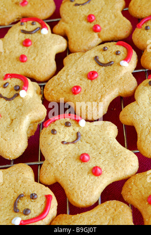 Lots of small gingerbread Santas cooling on a wire cooling rack. - Stock Photo
