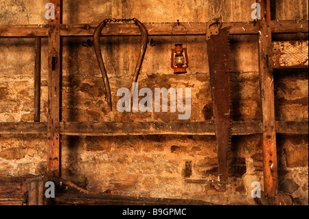 Old rusty tools hanging on stable wall - Stock Photo