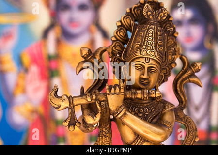 Metal Statue of Indian God Krishna Playing Flute with Colourful Indian Background - Stock Photo
