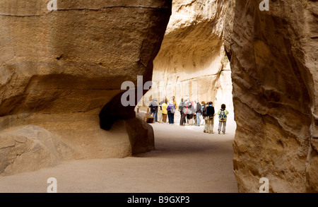 Tourists on a guided tour in the Siq, Petra, Jordan - Stock Photo