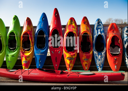 Row of colourful kayaks and canoes for sale Cardigan Town Ceredigion West Wales UK - Stock Photo