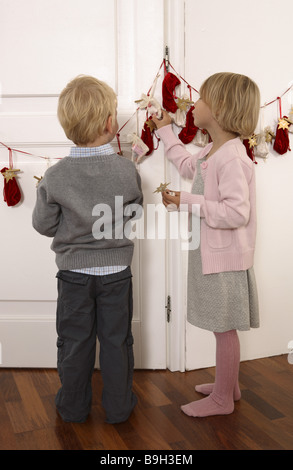 girl giving birth advent-calendars little sack back view feel lateral 4 years advent advent-calendar brother feeling - Stock Photo