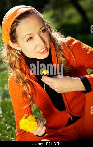 Blond lady on meadow graas with picked dandelion - Stock Photo