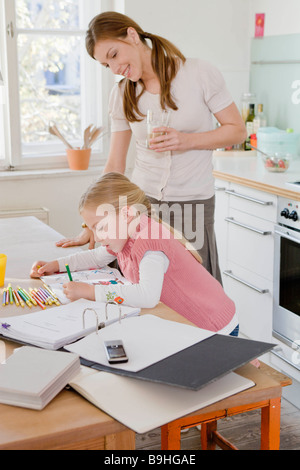 Girl and woman sitting at table working - Stock Photo