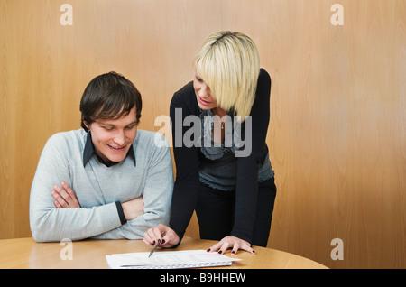 Young woman mentoring colleague - Stock Photo