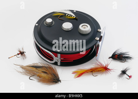 Reel with a red cast line and a variety of flies for fly fishing - Stock Photo