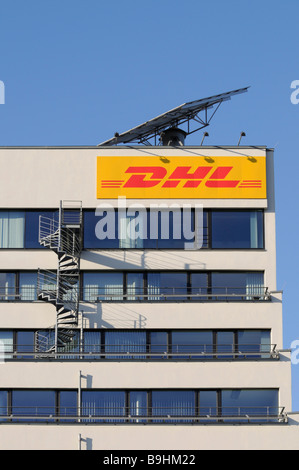 DHL logo on an office building, above it a mobile solar module, built-on fire stairs - Stock Photo