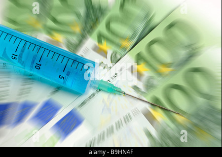 Injection needle on banknotes, symbolic picture for cash injection - Stock Photo