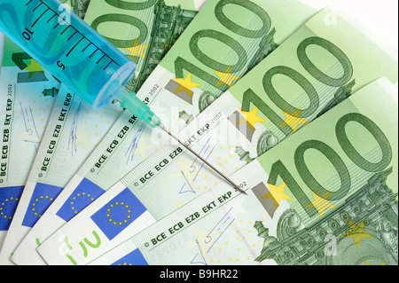 Injection needle on 100 euro banknotes, symbolic picture for cash injection, economy boost - Stock Photo