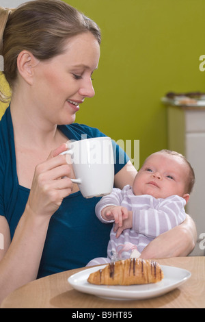 Young woman in coffee shop with baby - Stock Photo