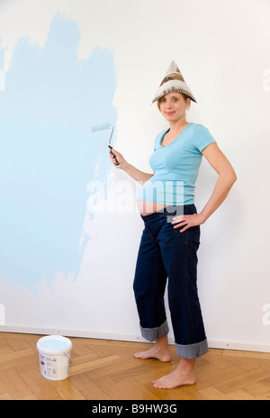 Pregnant woman painting nursery - Stock Photo