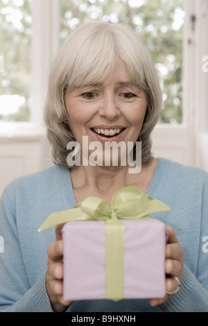 Senior gift holding cheerfully portrait series people seniors woman grey-haired birthday packet gets is amazed surprise - Stock Photo