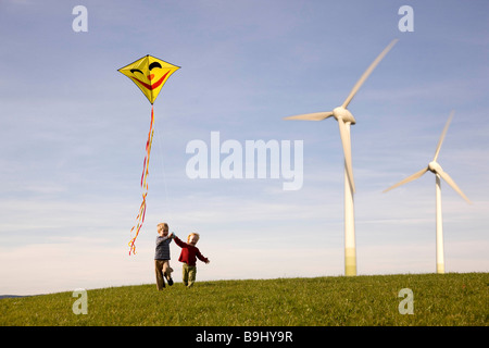 Two Boys Flying Kite at Wind Turbines - Stock Photo