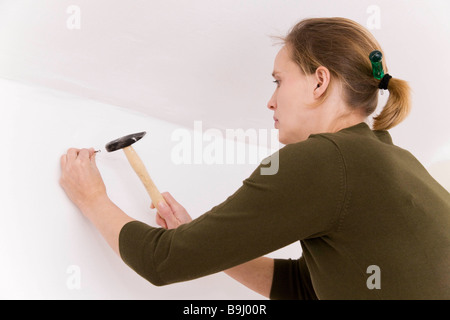 Woman with hammer and nail - Stock Photo