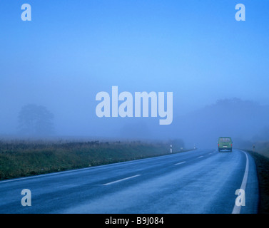 Country road in fog, car, Germany - Stock Photo