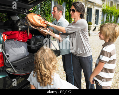 Family charging bags in the trunk - Stock Photo