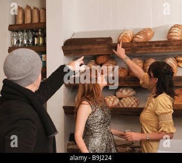 Man and woman pointing at bread on shelf - Stock Photo