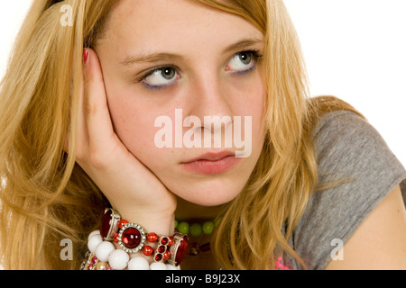 13-year-old girl leaning on her arm, dreamy or bored - Stock Photo