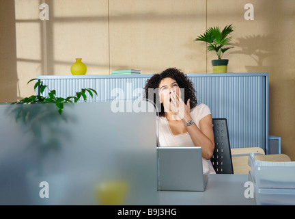 Woman yawning at desk in office - Stock Photo