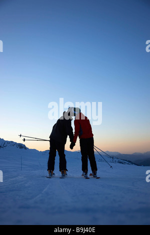Skiers kissing on top of mountain - Stock Photo