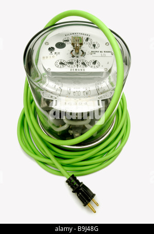 Electric power meter wrapped by a green electrical extension cord and plug - Stock Photo