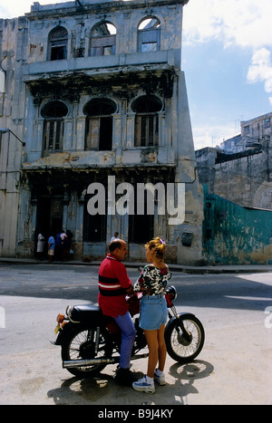 Woman talking to a man on a motorbike, streetscene in front of house ruins, San Lazaro, Centro Habana, Havana, Cuba, - Stock Photo
