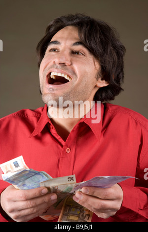 Young, happy man holding Euro banknotes - Stock Photo