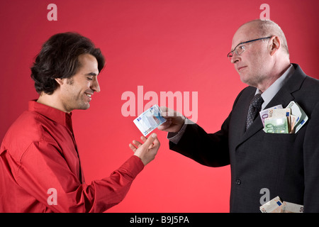 Rich businessman with full pockets offering young man money - Stock Photo