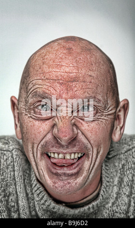 stylised portrait photograph of crazy bald man with his tongue sticking out - Stock Photo