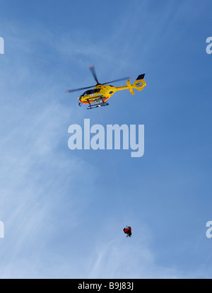 Rescue helicopter transporting injured people, on duty, Tyrol, Austria - Stock Photo