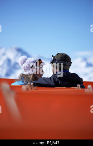 Couple sitting close in chair lift - Stock Photo