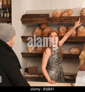 Woman pointing at bread on shelf - Stock Photo