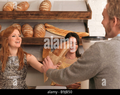 Woman handing bread to customer - Stock Photo