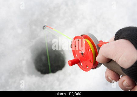 red ice fishing rod on hand - Stock Photo
