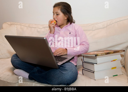 Student, approx. 11 years old, working on a laptop while eating an apple - Stock Photo