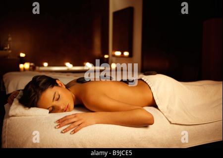 Woman receiving hot stone massage - Stock Photo