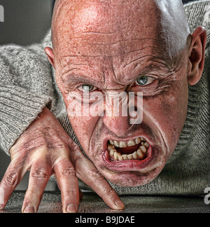stylised portrait photograph of scary crazy bald man snarling at the camera - Stock Photo