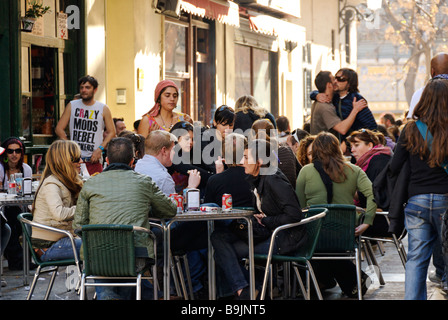 People sitting outside a busy cafe in El Carmen during las Fallas festival historic city centre of Valencia Spain - Stock Photo