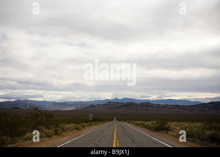 A road continues straight into the distance in Death Valley National Park, California. - Stock Photo