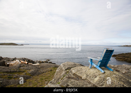 A lawn chair sits atop a rock outcrop overlooking the ocean on an overcast day in Victoria, British Columbia, Canada. - Stock Photo