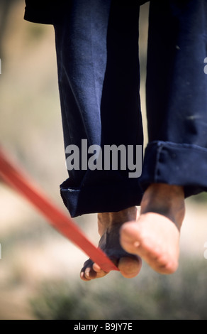 Close up of a man's bare feet balancing on a tight rope or slackline in the California desert. - Stock Photo