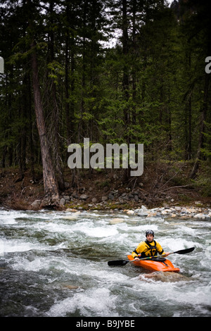 A male kayaker sits in an eddy facing upstream in the middle of a river. - Stock Photo