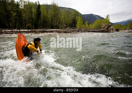 A playboater enjoys a small wave on a river. - Stock Photo