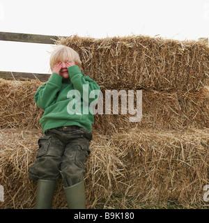 Boy hiding eyes on hay bales - Stock Photo