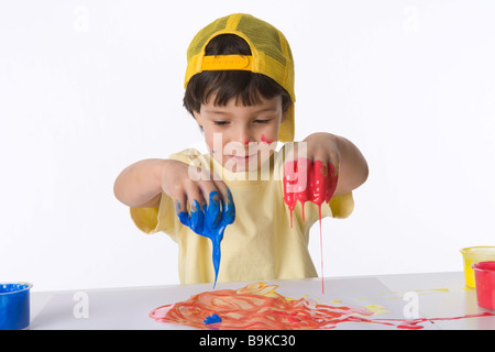 Little boy is making a finger painting - Stock Photo